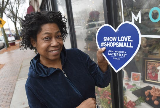 Kay Willingham, owner of Art in Motion, shows her pride in promoting Small Business Saturday along the Avenue of Fashion on Livernois Avenue near 7 Mile Road on November 24, 2018