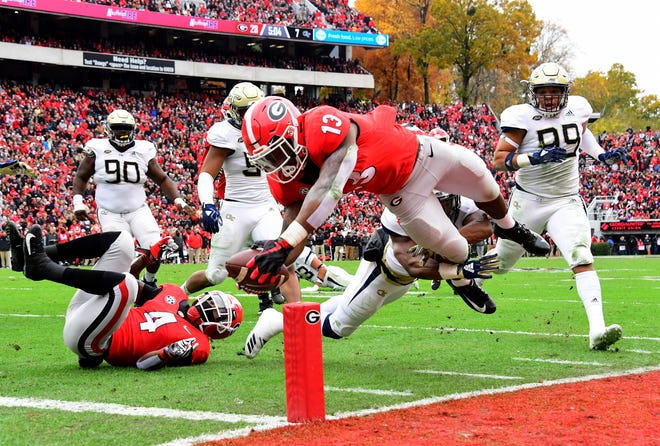 Georgia's Elijah Holyfield (13) scores a second-quarter touchdown against Georgia Tech Saturday at Sanford Stadium in Athens, Georgia.