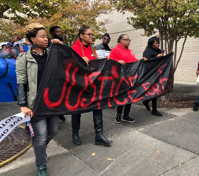 "Protestors carry a sign reading ""Justice for E.J."" during a protest at the Riverchase Galleria in Hoover, Ala., Saturday, Nov. 24, 2018."