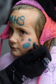 Erin Bates paints her four-year-old daughter Grace Bates's face during a Memorial Tigers tailgate party in the South parking lot of Lucas Oil Stadium, Saturday, Nov. 24, 2018. The Memorial Tigers competed against the West Lafayette Red Devils in the IHSAA Class 3A state championship.