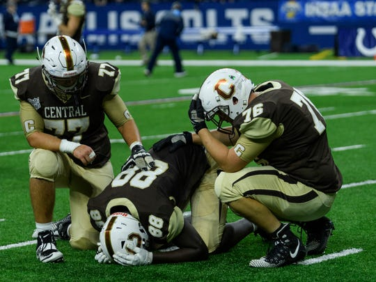 Central's Kody Martin (77) and Dalton Mills (76) comfort their teammate Rayzel Joiner (88) after falling 16-10 to the Fort Wayne Bishop Dwenger Saints in a fourth overtime in the IHSAA Class 4A state championship at Lucas Oil Stadium in Indianapolis, Ind., Friday, Nov. 23, 2018.
