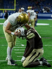 Bishop Dwenger's Grant Sorg (51) gives Central's Rayzel Joiner (88) a pat on the back following the Bears' 16-10 loss in a fourth overtime state championship match at Lucas Oil Stadium in Indianapolis, Ind., Friday, Nov. 23, 2018.