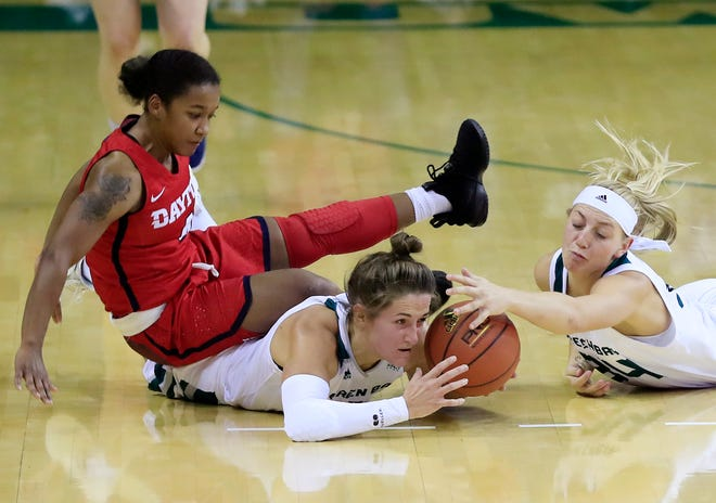 Phoenix guard Jen Wellnitz (1), forward Carly Mohns (34) and Dayton Flyers guard Shakeela Fowler (4) dive for a loose ball in a during UWGB's 51-35 win at the Kress Center on Saturday.