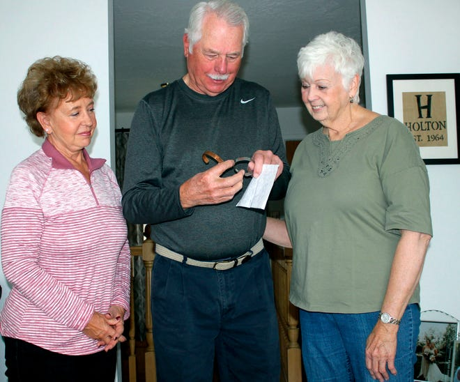 In this 2018 photo, from left, Judy Holton, Bill Holton and Sue MacPherson look over POW/MIA bracelets they recently received with the name of Capt. Robert Holton and the date he went missing during the Vietnam War, in Butte, Mont.  Capt. Holton's remains were found in Laos last year, verified, and returned to Butte. (Mike Smith /The Montana Standard via AP)