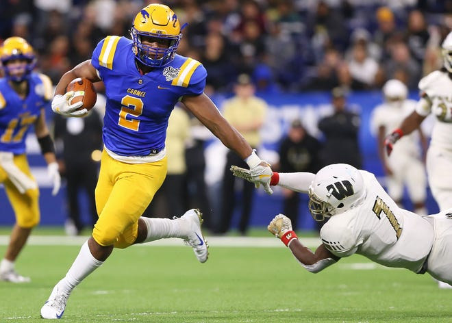 Carmel's Dylan Downing (2) runs the ball past Warren Central's Isaiah Warren (7) in the first half of the IHSAA Class 6A state final game at Lucas Oil Stadium in Indianapolis, Ind., Friday, Nov. 23, 2018.