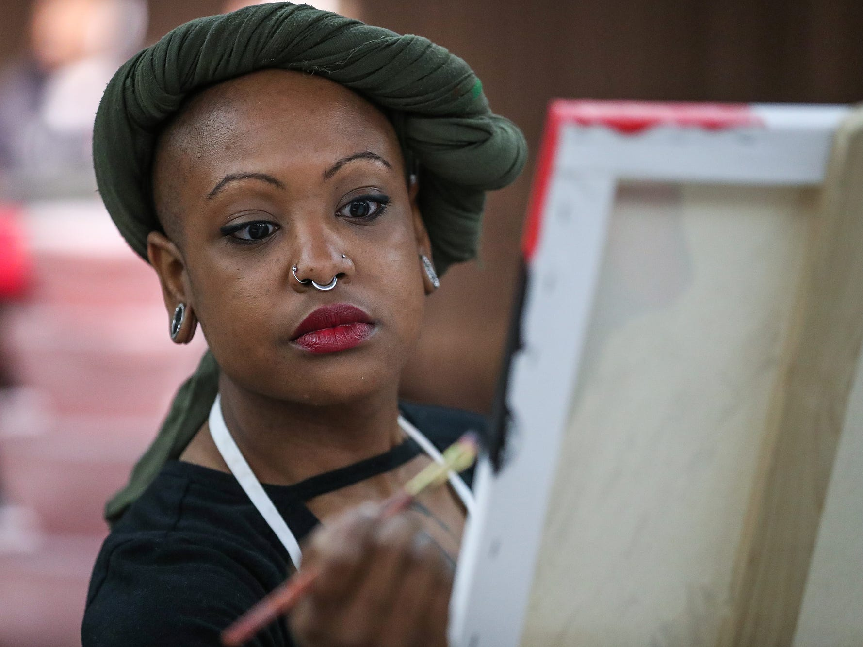 Artist Deonna Craig works on a painting during a market showcasing more than 65 women and minority-owned small businesses at the Murat Shrine Temple in Indianapolis, Saturday, Nov. 24, 2018. The fifth annual event is part of Small Business Saturday, launched nationally by American Express eight years ago to help independently owned businesses bounce back from the recession.