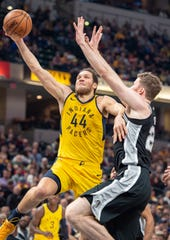 Indiana Pacers forward Bojan Bogdanovic (44) drives the ball to the basket around the defense of San Antonio Spurs center Jakob Poeltl (25) during the first half of an NBA basketball game in Indianapolis, Friday, Nov. 23, 2018.