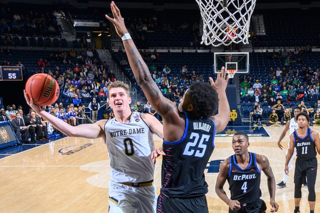 Notre Dame Fighting Irish guard Rex Pflueger (0) shoots against DePaul Blue Demons forward Femi Olujobi (25) in the second half at the Purcell Pavilion.