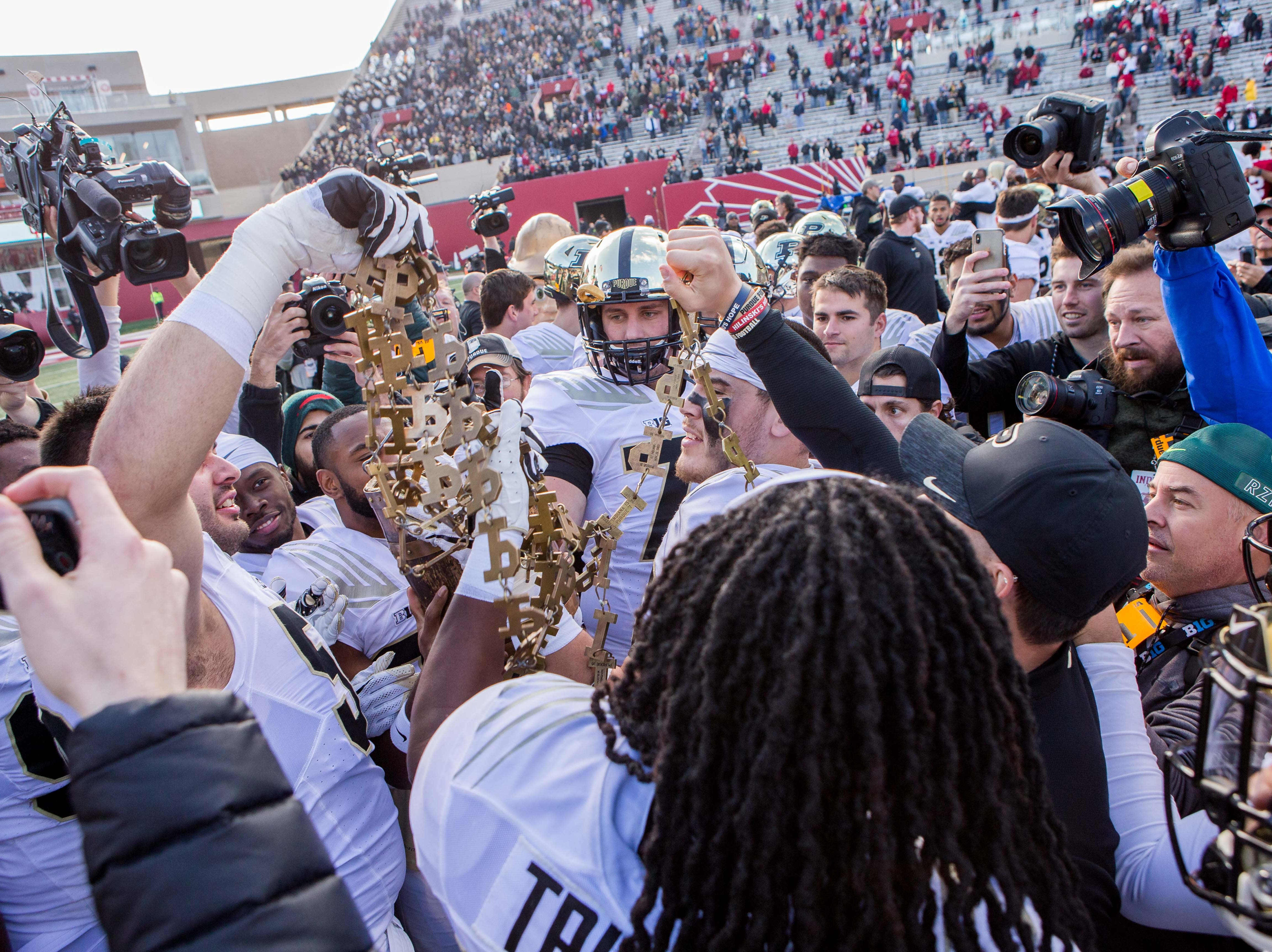 Purdue Boilermakers players pull the chain out of the old oak bucket after a game against the Indiana Hoosiers at Memorial Stadium.