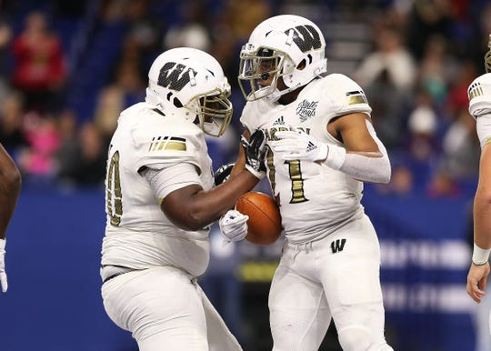 Warren Central's Romeir Elliott (21) celebrates a touchdown against Carmel in the first half of the IHSAA Class 6A state final game at Lucas Oil Stadium in Indianapolis, Ind., Friday, Nov. 23, 2018.
