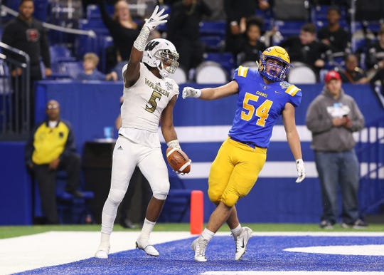 Warren Central's tight end Montrez Stanley (5) celebrates a touchdown against Carmel's defensive end Jack Knapp (54) in the first half of the IHSAA Class 6A state final game at Lucas Oil Stadium in Indianapolis, Ind., Friday, Nov. 23, 2018.