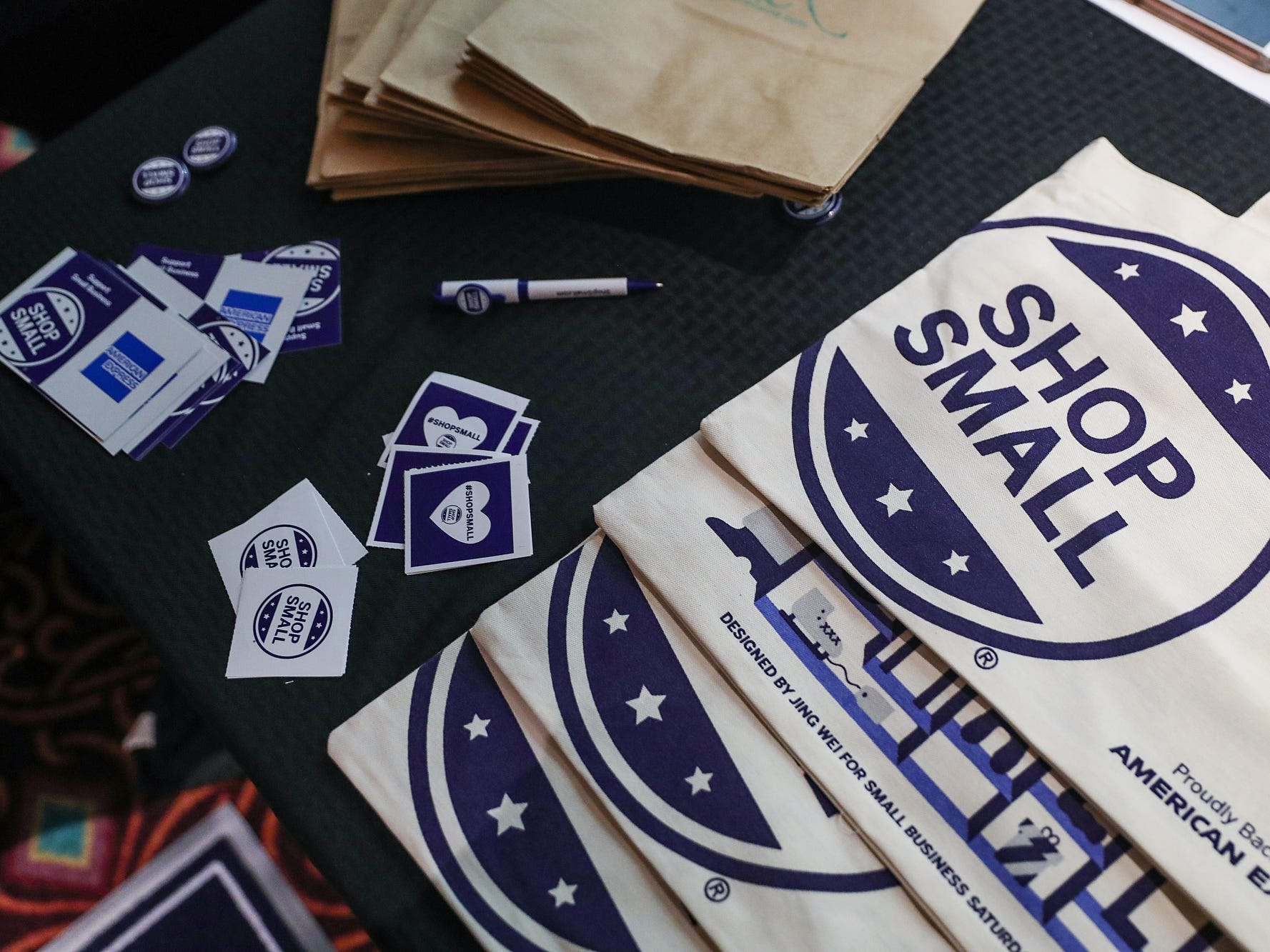 Bags and stickers are given away at a market showcasing more than 65 women and minority-owned small businesses at the Murat Shrine Temple in Indianapolis, Saturday, Nov. 24, 2018. The fifth annual event is part of Small Business Saturday, launched nationally by American Express eight years ago to help independently owned businesses bounce back from the recession.
