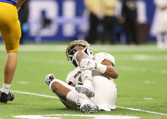 Warren Central's Hunter Shanklin holds his leg after being injured on a play against Carmel in the Class 6A state final game at Lucas Oil Stadium, Nov. 23, 2018.