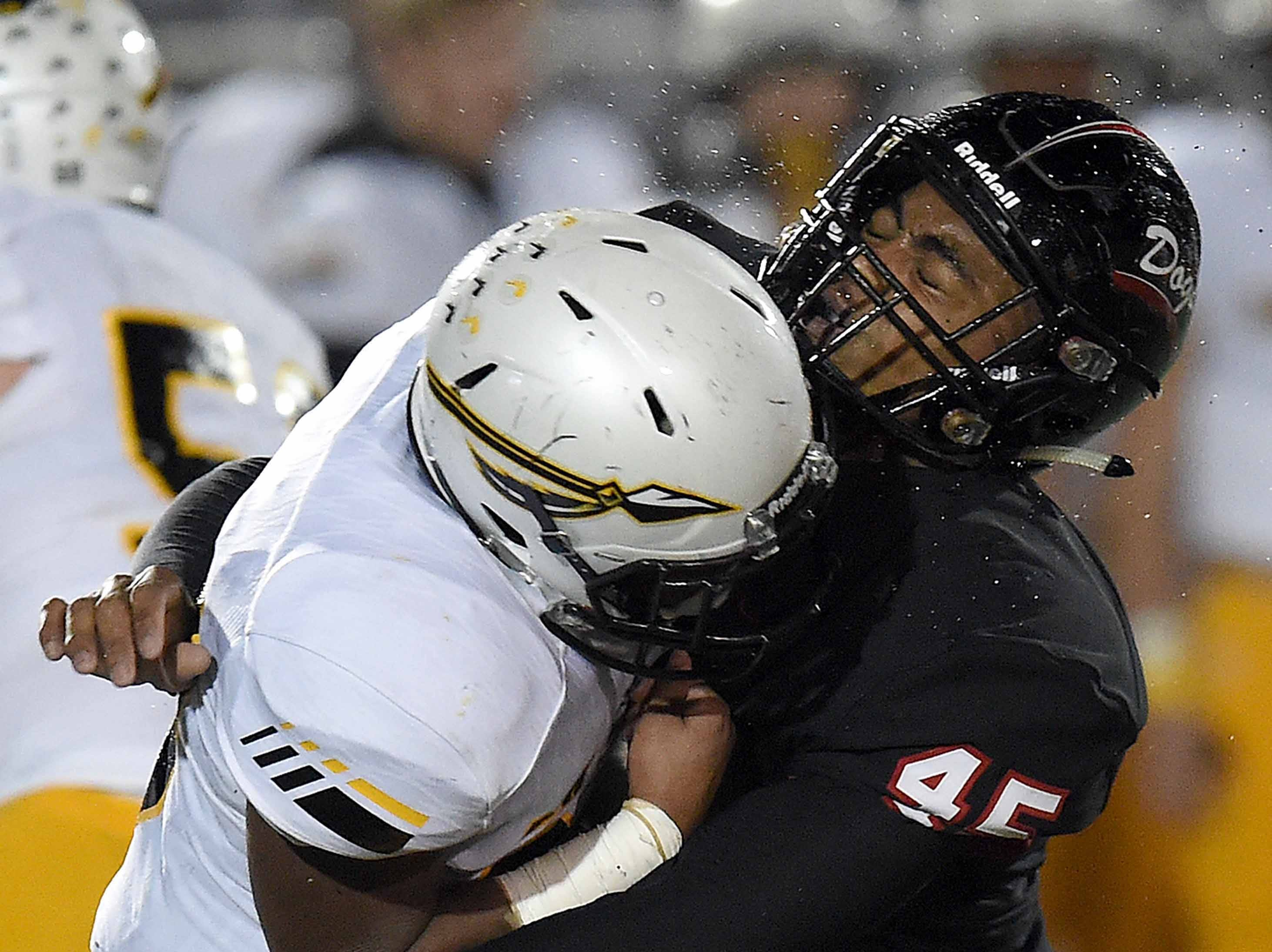 Water flies off the helmet of Brandon's Orvin Gipson (45) after making a hit on an Oak Grove ball carrier in the MHSAA Class 6A South State Championship on Friday, November 23, 2018, at Brandon High School in Brandon, Miss.