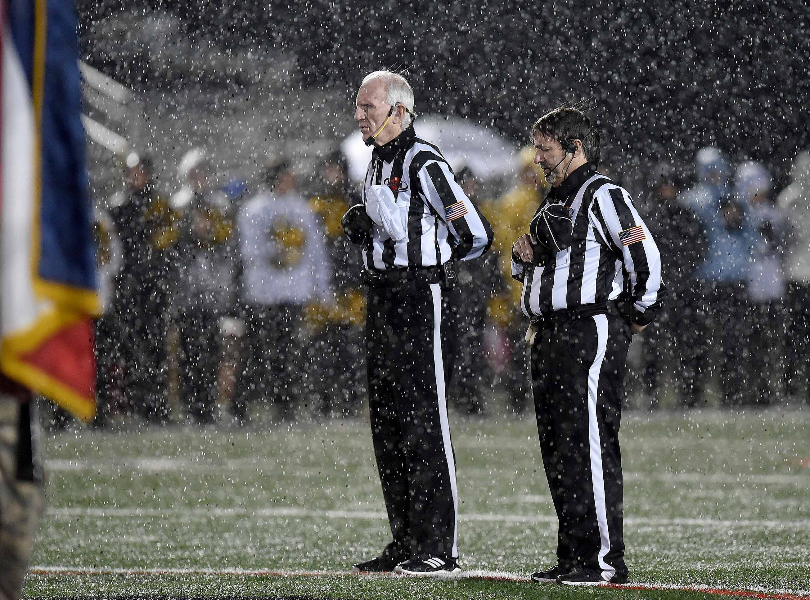 Two officials honor the flag during the National Anthem the MHSAA Class 6A South State Championship on Friday, November 23, 2018, at Brandon High School in Brandon, Miss.