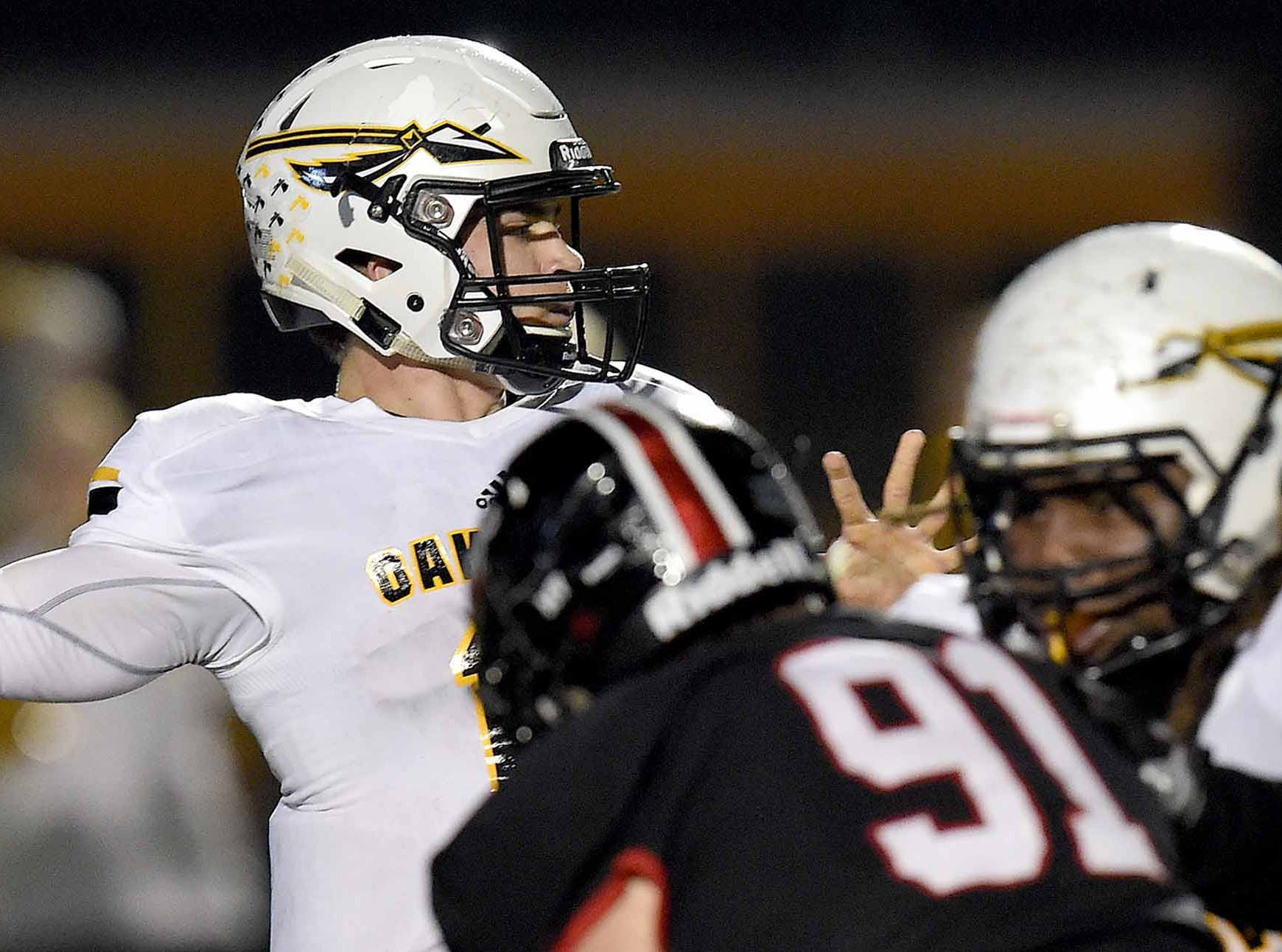 Oak Grove quarterback John Rhys Plumlee (left) throws over the Brandon pass rush in the MHSAA Class 6A South State Championship on Friday, November 23, 2018, at Brandon High School in Brandon, Miss.