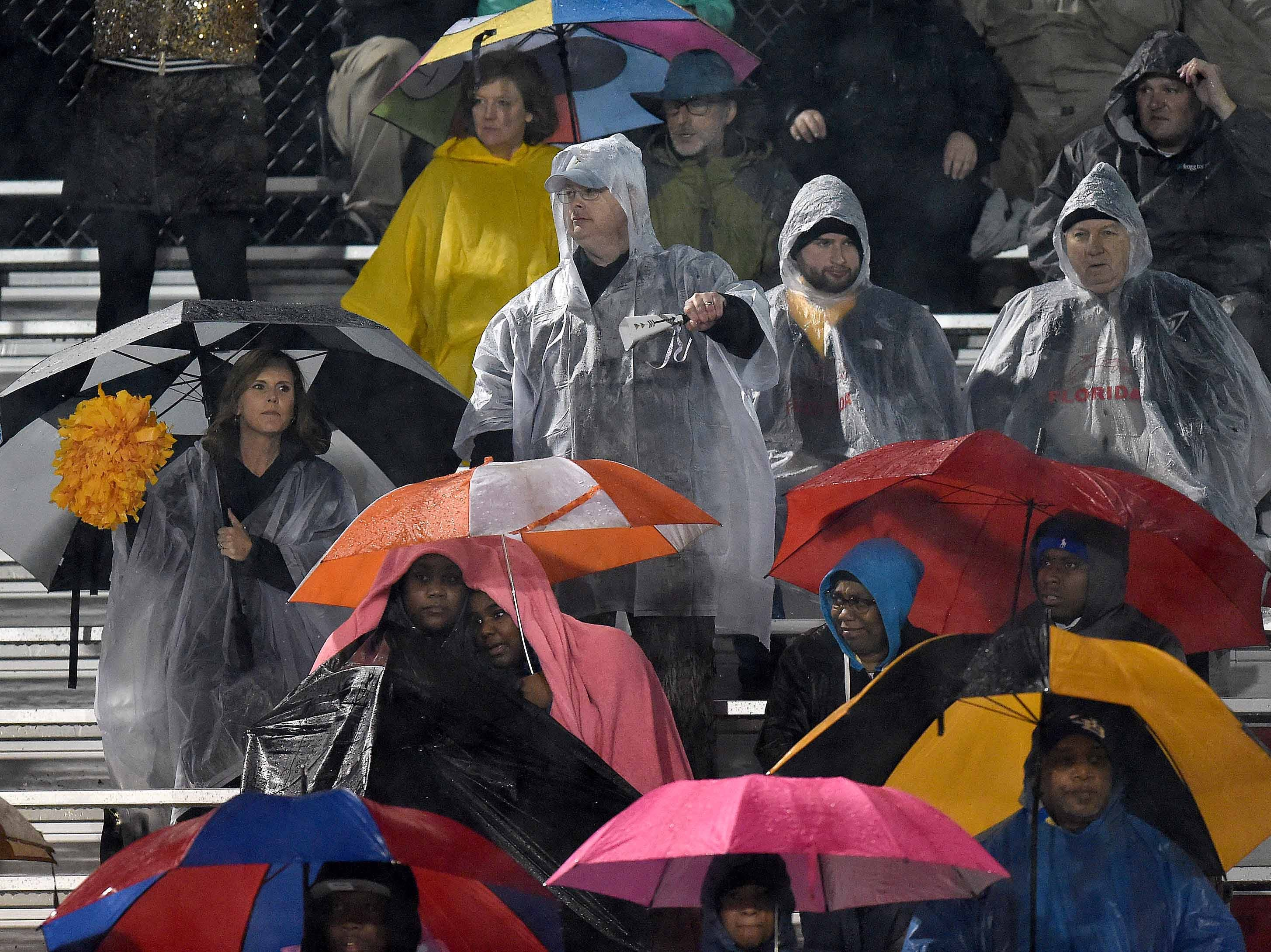 Oak Grove fans use umbrellas and rain gear early in the MHSAA Class 6A South State Championship on Friday, November 23, 2018, at Brandon High School in Brandon, Miss.