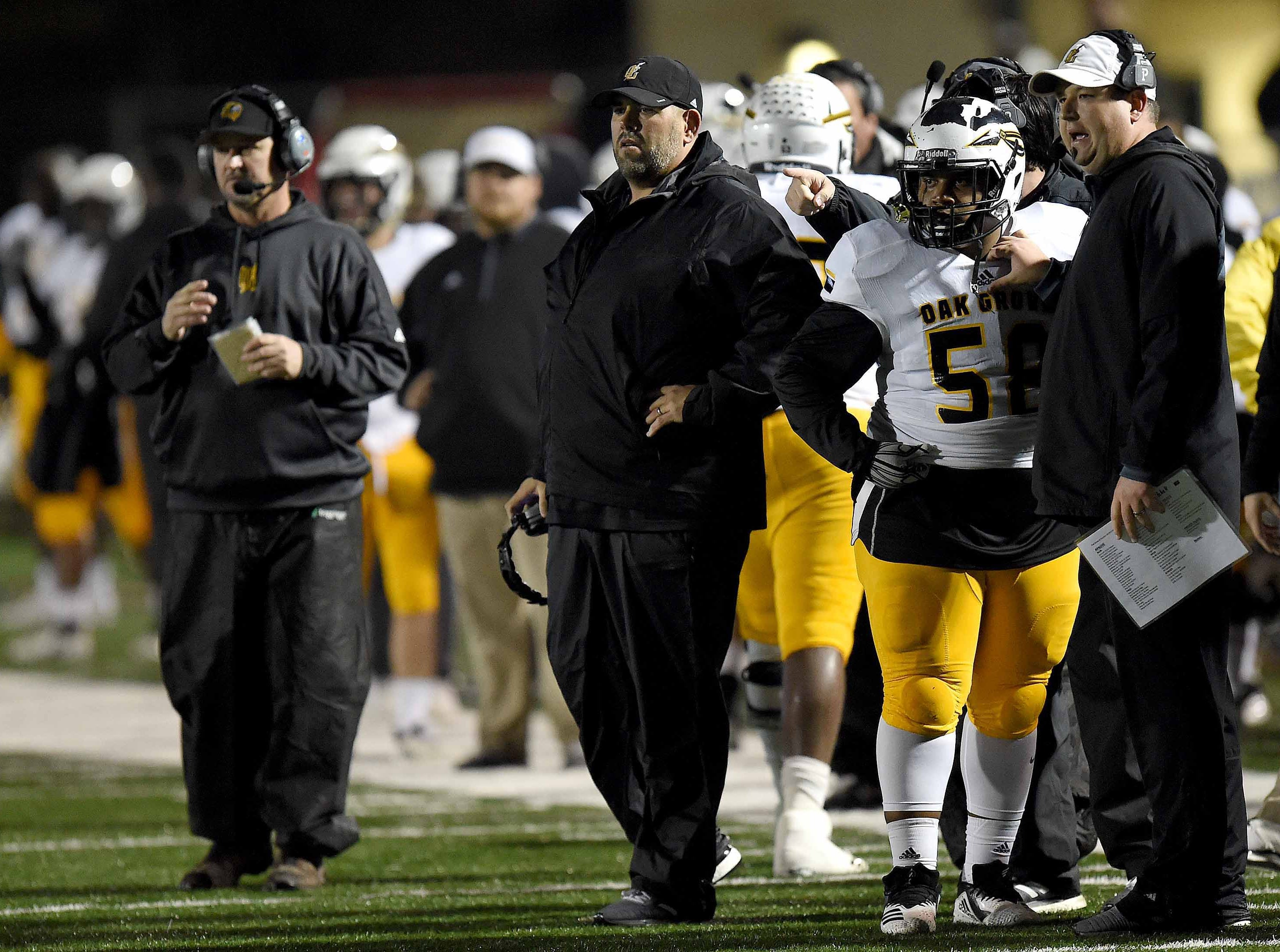 Oak Grove head coach Drew Causey (center) and his staff watch an extra point in the MHSAA Class 6A South State Championship on Friday, November 23, 2018, at Brandon High School in Brandon, Miss.