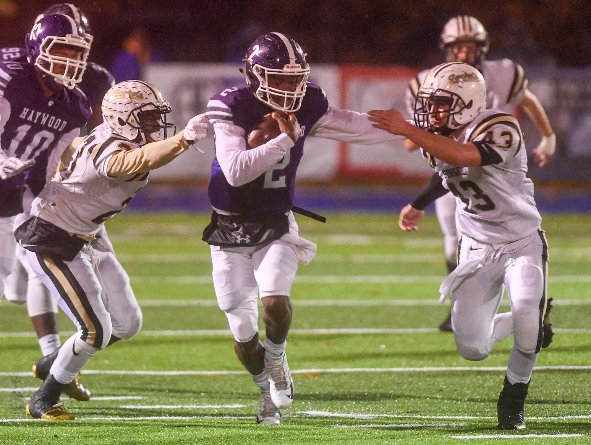 Springfield defenders attempt to tackle Haywood's Deyondrius Hines during their Class 4A semifinal game, Friday, November 23. Haywood lead at the half, 14-7.