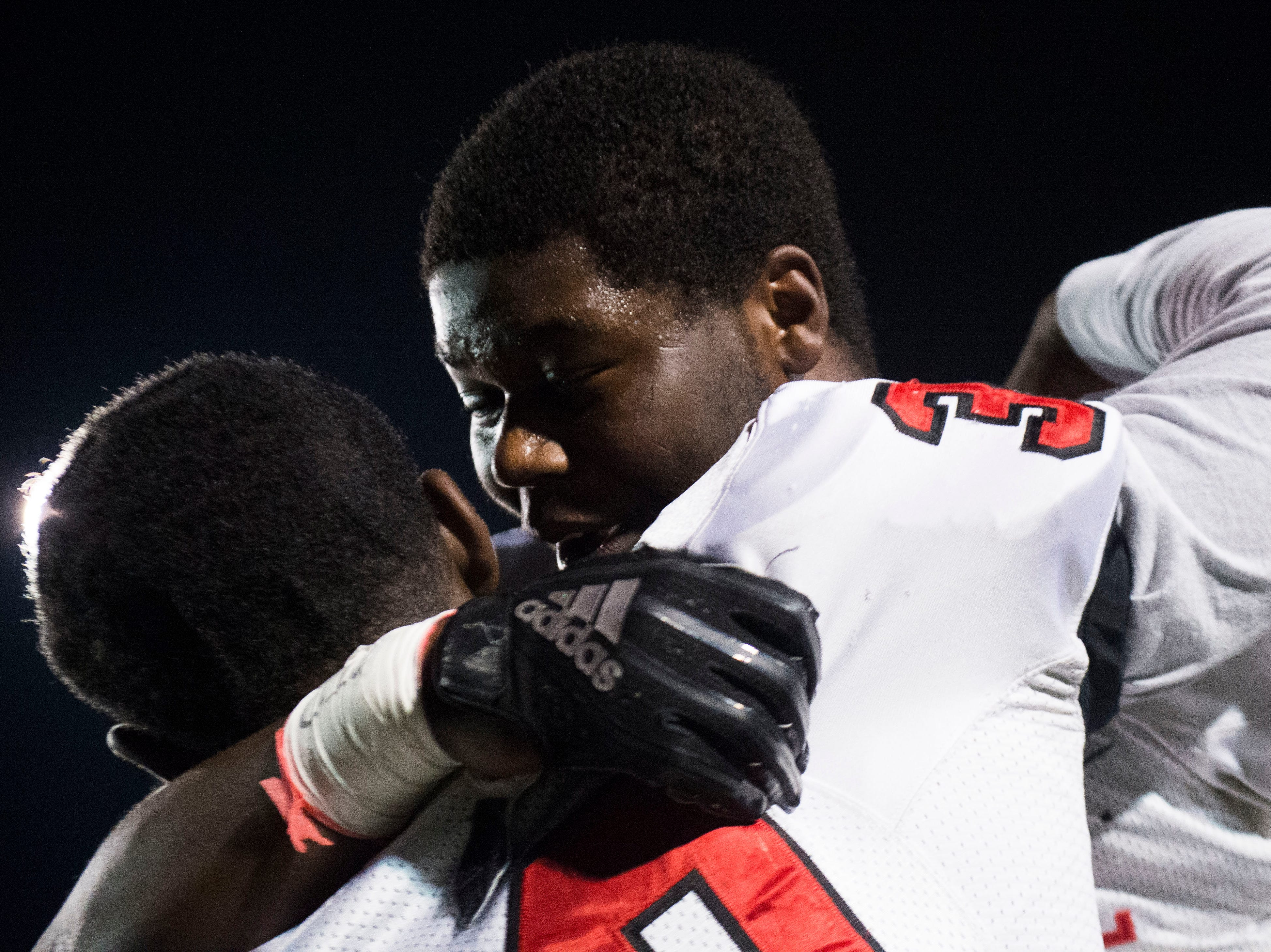 At left Central's Mark Adams (37) hugs a teammate after a Class 5A semifinal game between Central at Catholic Friday, Nov. 23, 2018. Central defeated Catholic 24-19.
