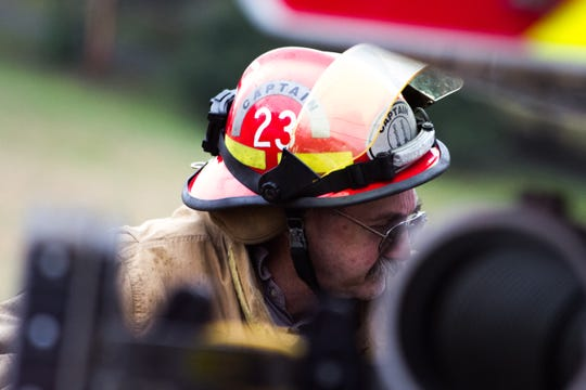 Capt. Johnny Leatherwood of the Blount County Fire Protection District goes back to the truck while battling a blaze in the 200 block of Shelby Drive on Saturday.