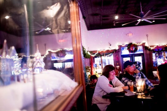 Patrons site beside a decorated jewelry display case at Sapphire on Gay Street in Knoxville, Tennessee on Friday, November 23, 2018. Sapphire is transforming into a Christmas-themed bar through December starting Black Friday.