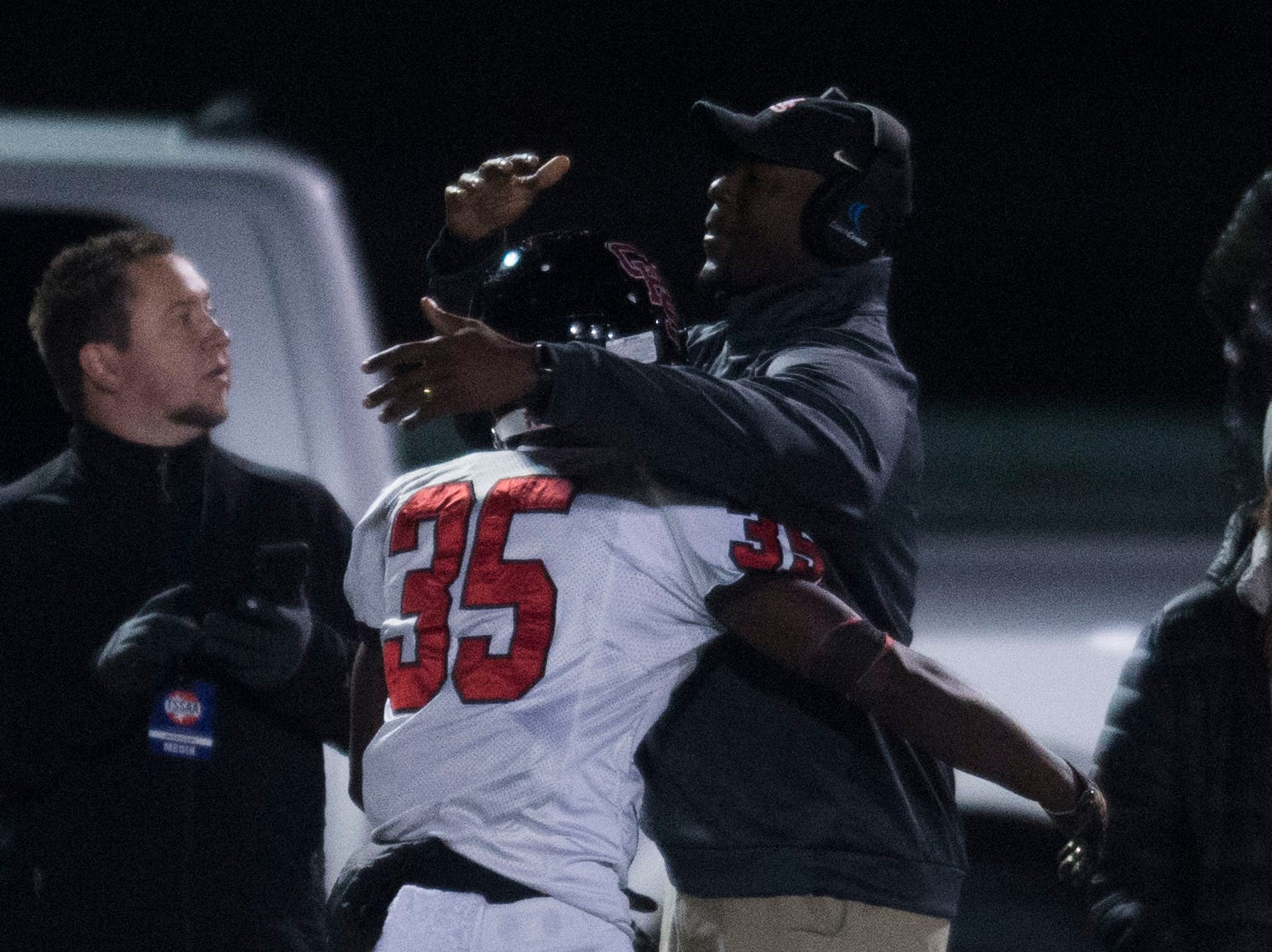 Central head coach Bryson Rosser hugs player Jason Merritts (35) after his touchdown, the first of the game, during a Class 5A semifinal game between Central at Catholic Friday, Nov. 23, 2018. Central defeated Catholic 24-19.