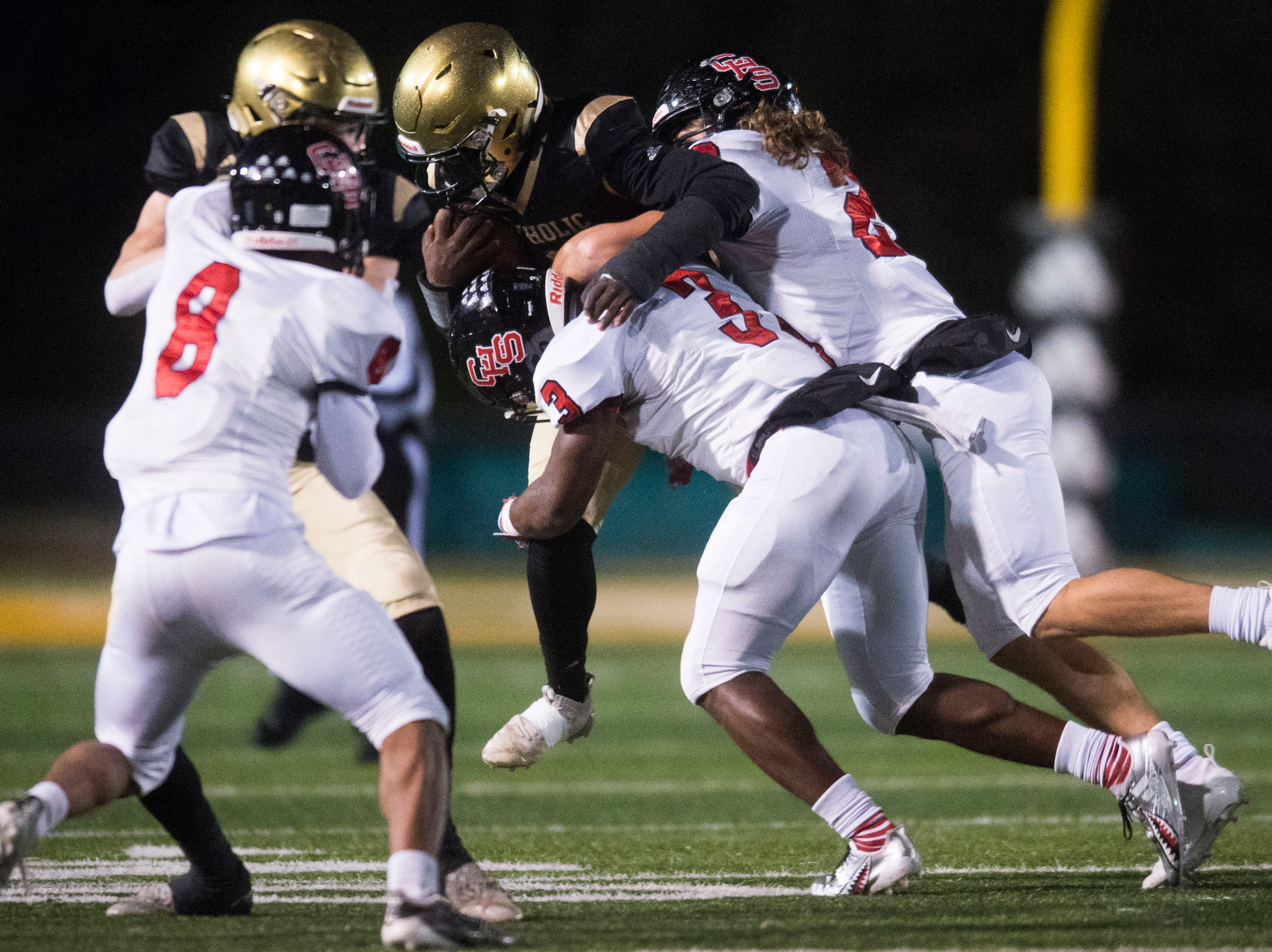 Central players take down a Catholic player during a Class 5A semifinal game between Central at Catholic Friday, Nov. 23, 2018. Central defeated Catholic 24-19.