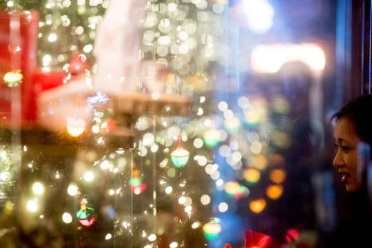 Christmas lights are reflected in window panes at Sapphire on Gay Street in Knoxville, Tennessee on Friday, November 23, 2018. Sapphire is transforming into a Christmas-themed bar through December starting Black Friday.