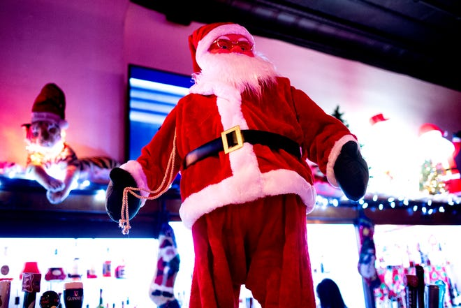 Santa Claus stands on the bar at Sapphire on Gay Street in Knoxville, Tennessee on Friday, November 23, 2018. Sapphire is transforming into a Christmas-themed bar through December starting Black Friday.