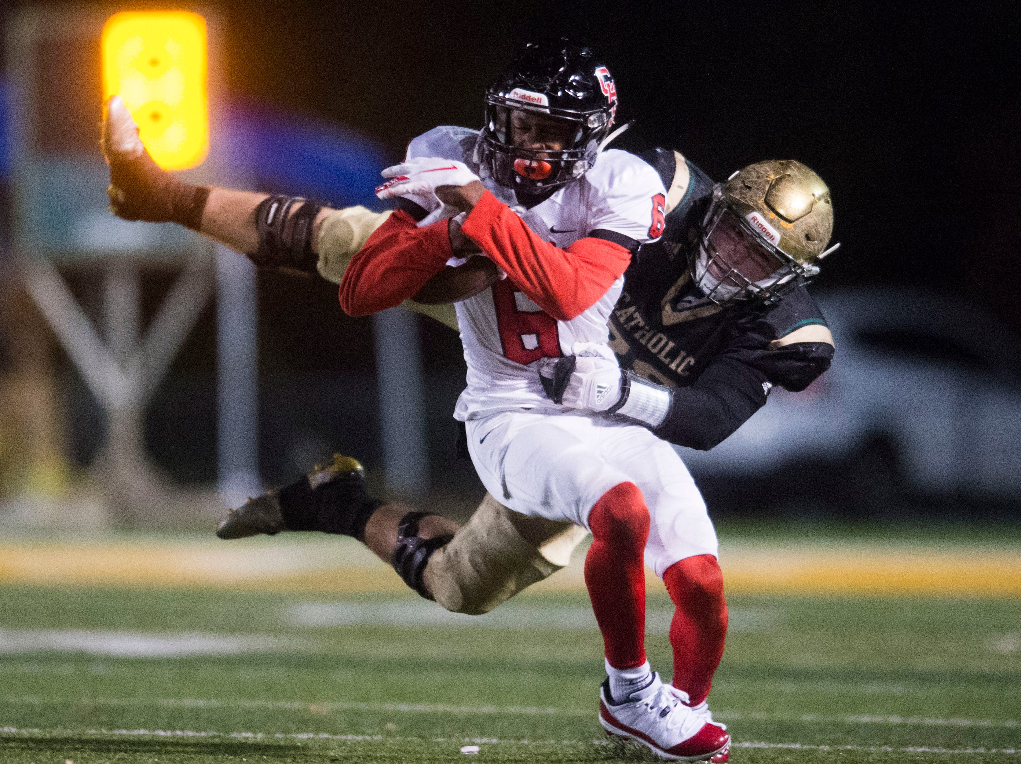 Central's Demetrien Johnson (6) is taken down by a Catholic player during a Class 5A semifinal game between Central at Catholic Friday, Nov. 23, 2018. Central defeated Catholic 24-19.