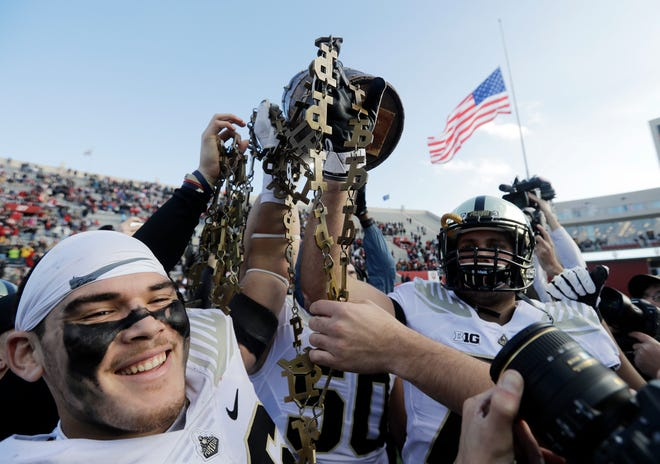 Purdue's Ray Ellis, left, holds the Old Oaken Bucket with his teammates after Purdue defeated Indiana, 28-21, in an NCAA college football game, Saturday, Nov. 24, 2018, in Bloomington, Ind. (AP Photo/Darron Cummings)