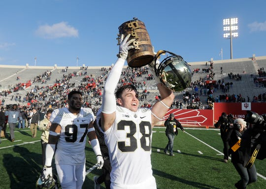 Purdue's Brennan Thieneman holds the Old Oaken Bucket after Purdue defeated Indiana, 28-21, in an NCAA college football game, Saturday, Nov. 24, 2018, in Bloomington, Ind. (AP Photo/Darron Cummings)