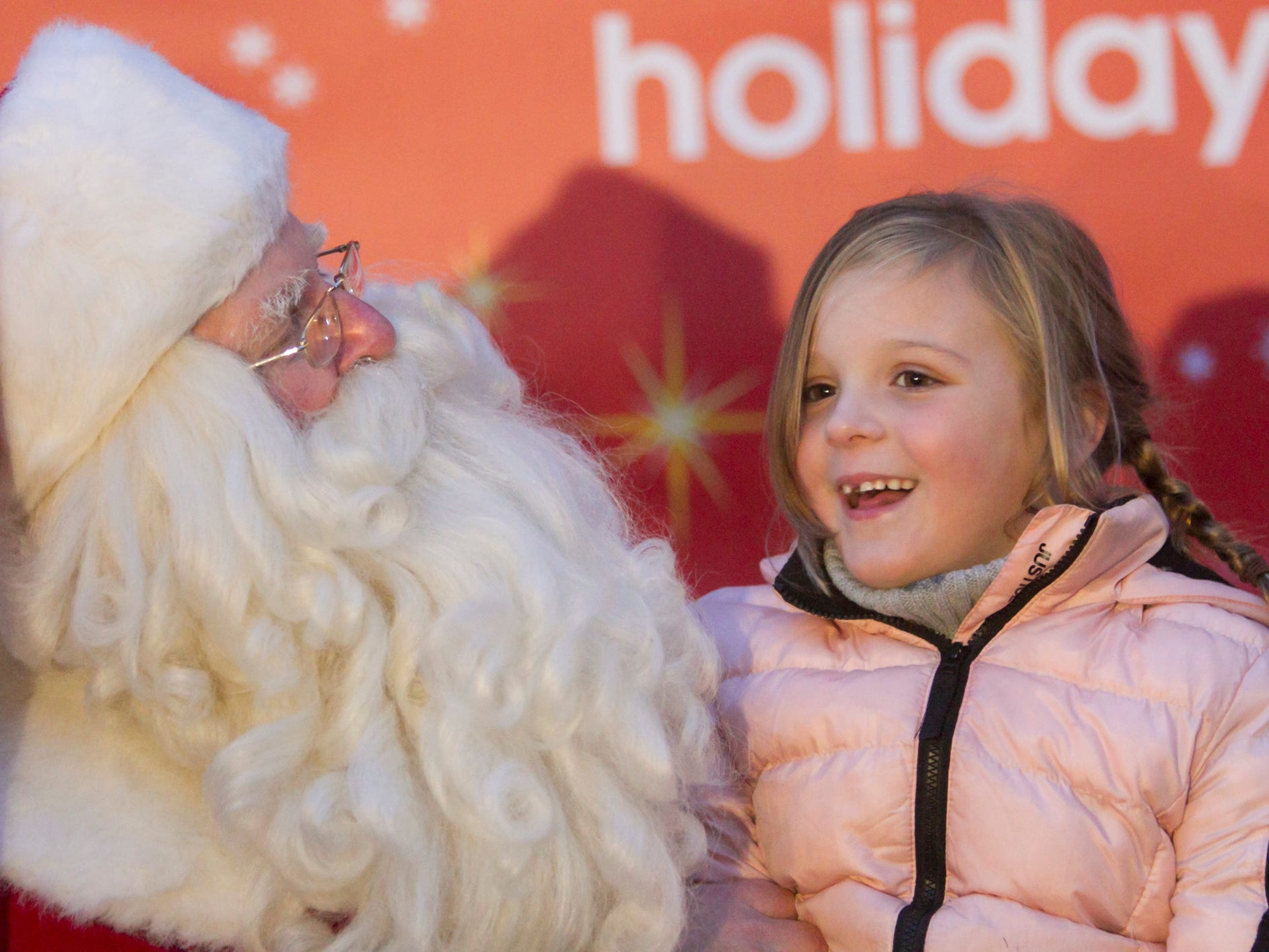 6-year-old Lily Adkins tells Santa her Christmas wishes before Santa takes to his sleigh in the Fantasy of Lights parade in Howell Friday, Nov. 23, 2018.
