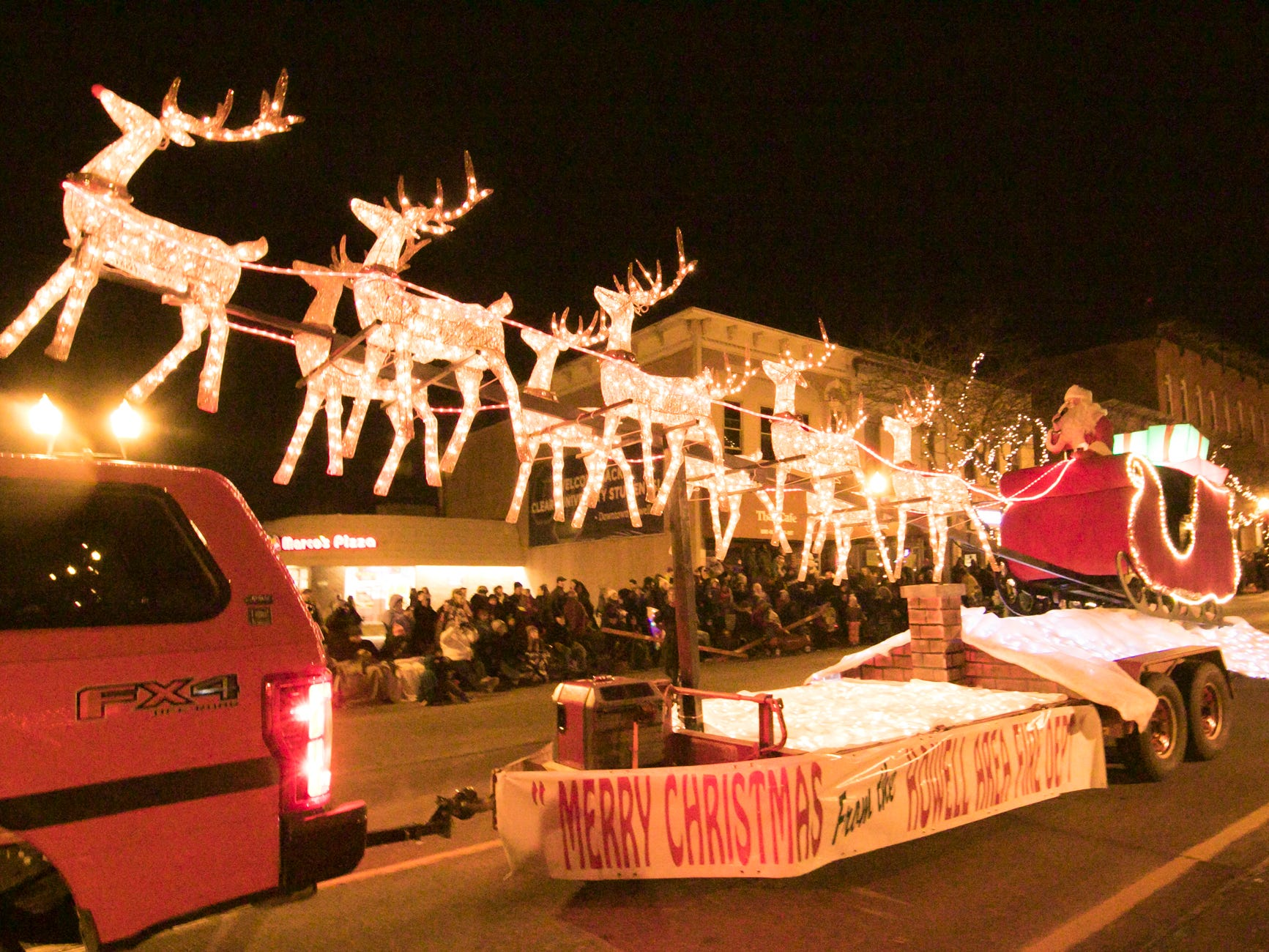 Santa arrives in a float provided by the Howell Area Fire Department in the Fantasy of Lights parade Friday, Nov. 23, 2018.