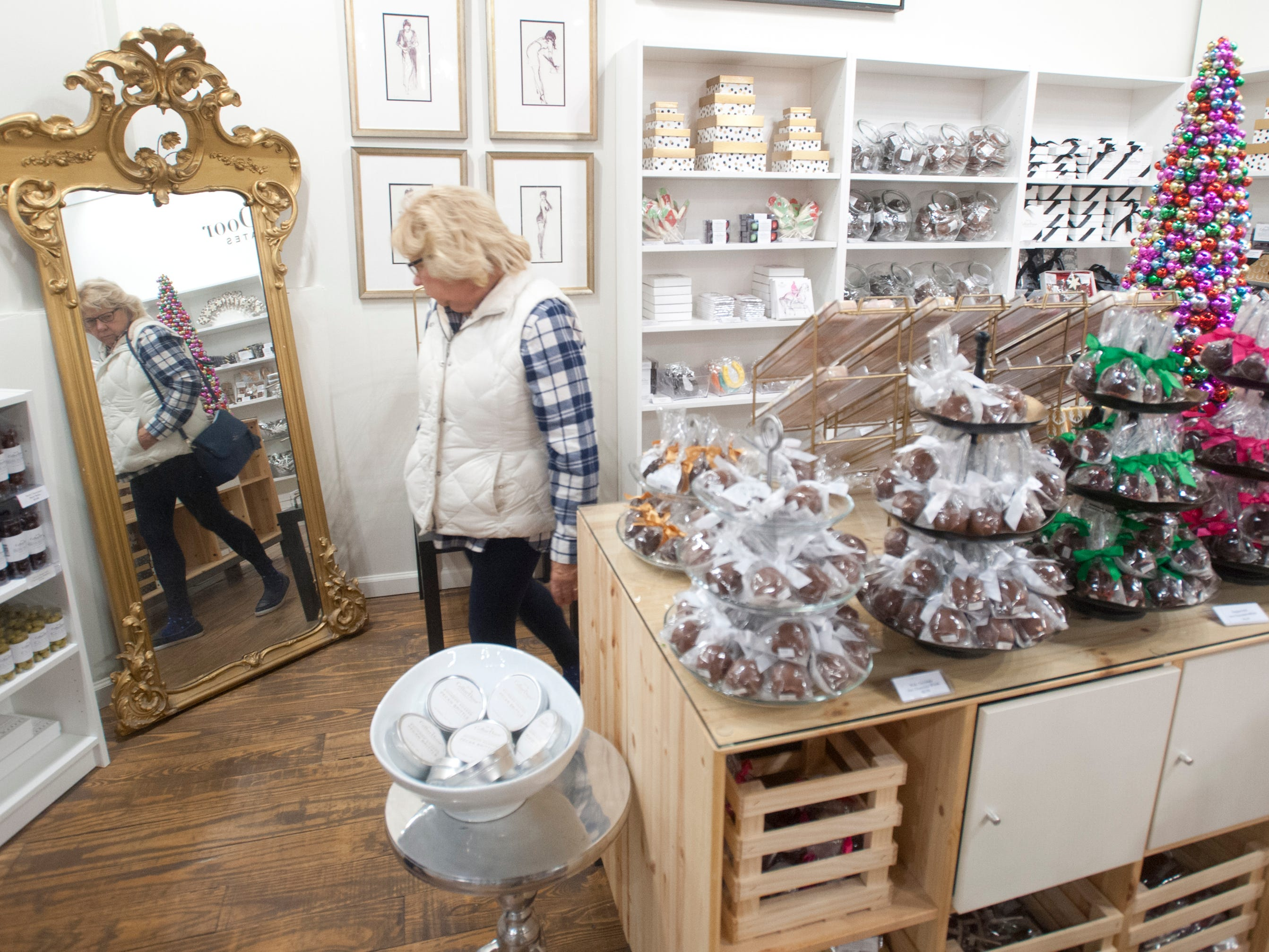Linda Lorch of New Albany passes an antique mirror as she shops in Cellar Door, a candy shop at 1201 Story Ave. as part of Louisville's Small Business Saturday.24 November 2018