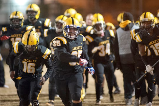 Central linebacker Benjamin Bush leads his team onto the field as Central takes on LaRue County in the 3A semifinal game. Nov. 23, 2018