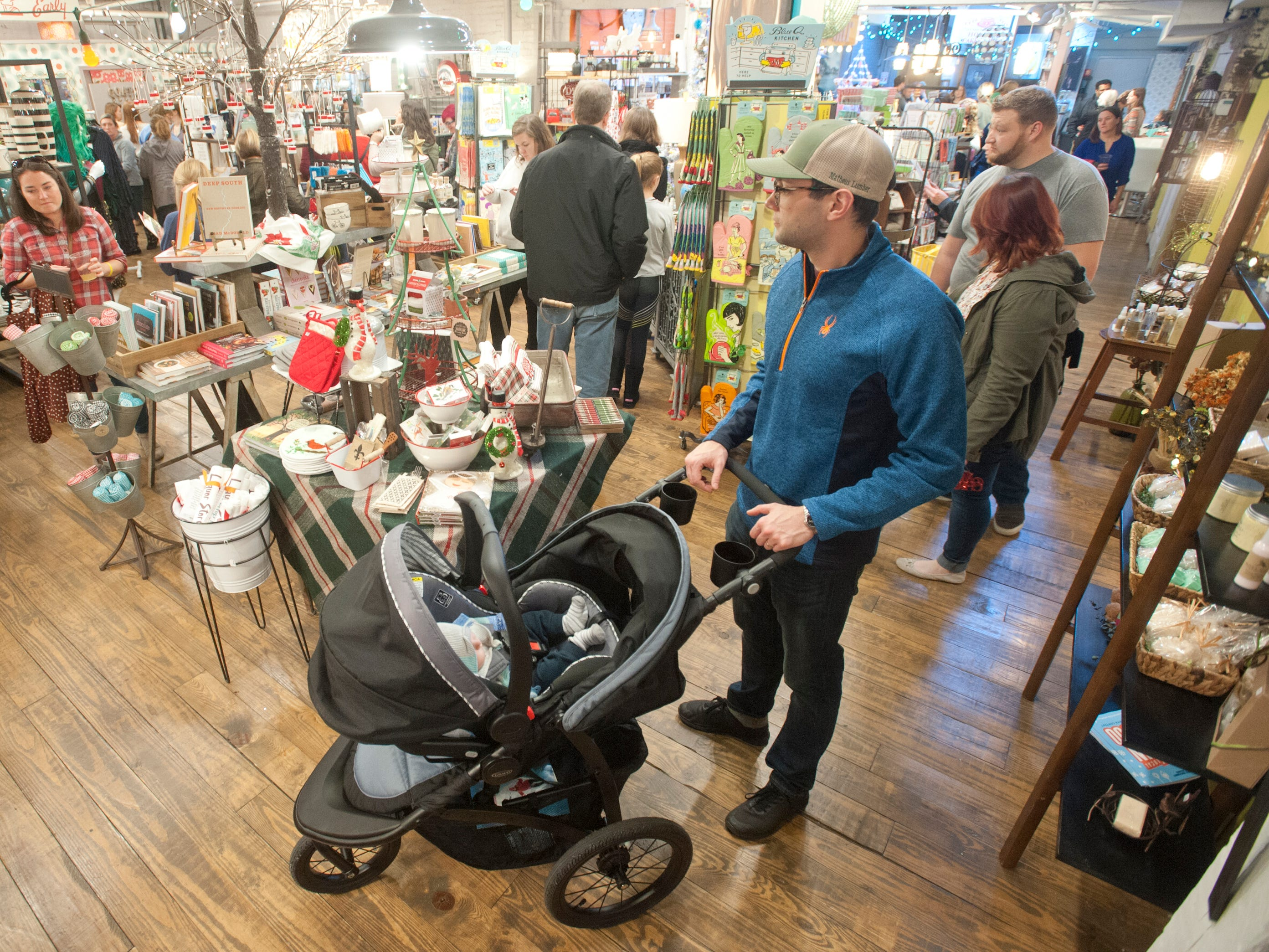 Austin English of the Brownsboro Farms neighborhood, wheels his 3-month old son, Oliver, about in the Work The Metal boutique at 1201 Story Ave. 24 November 2018