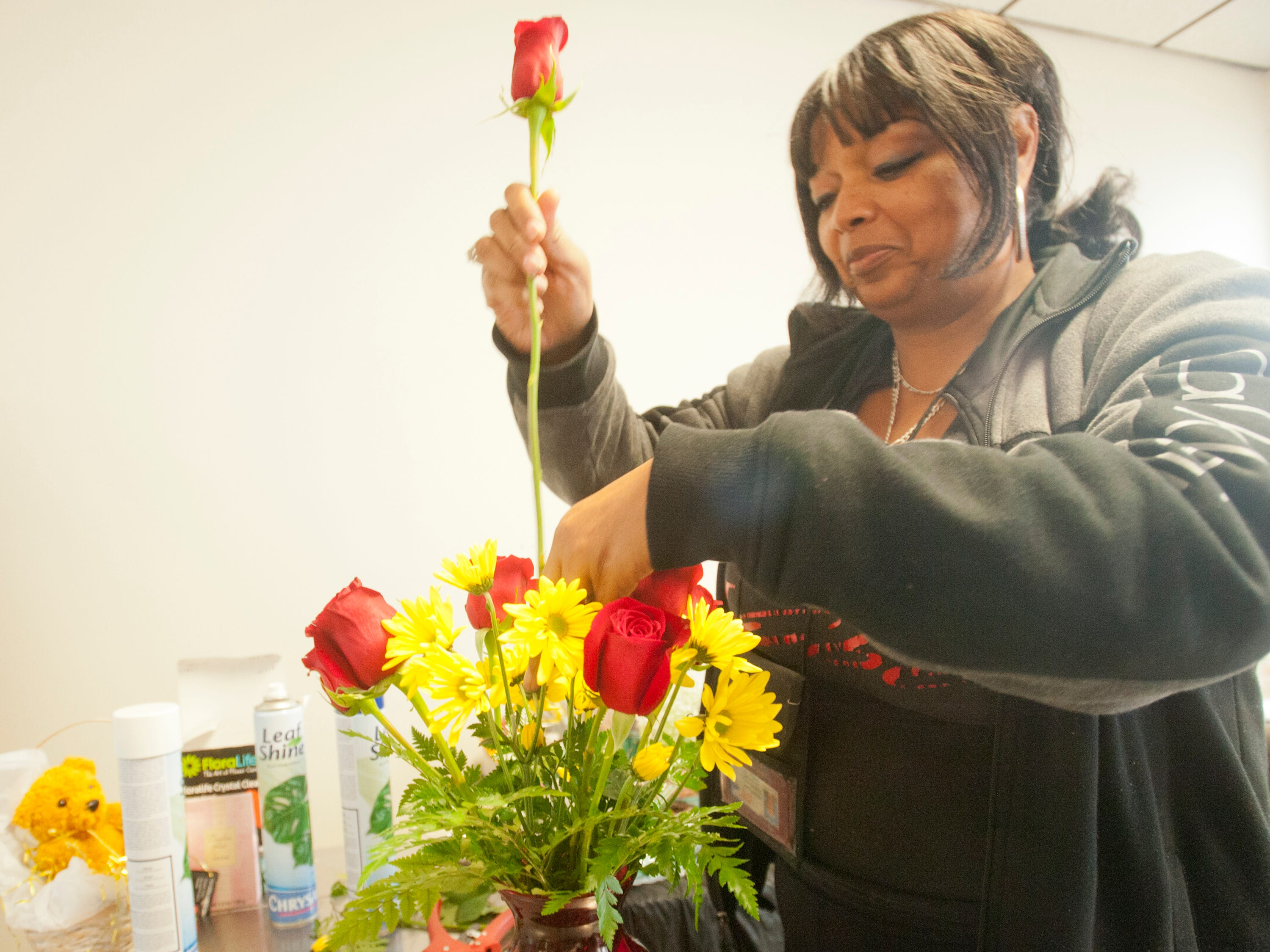 D.N. Surprise Florist Shop co-owner Sherrell Anderson prepares a floral arrangement at her store at 2001 W. Broadway. 24 November 2018