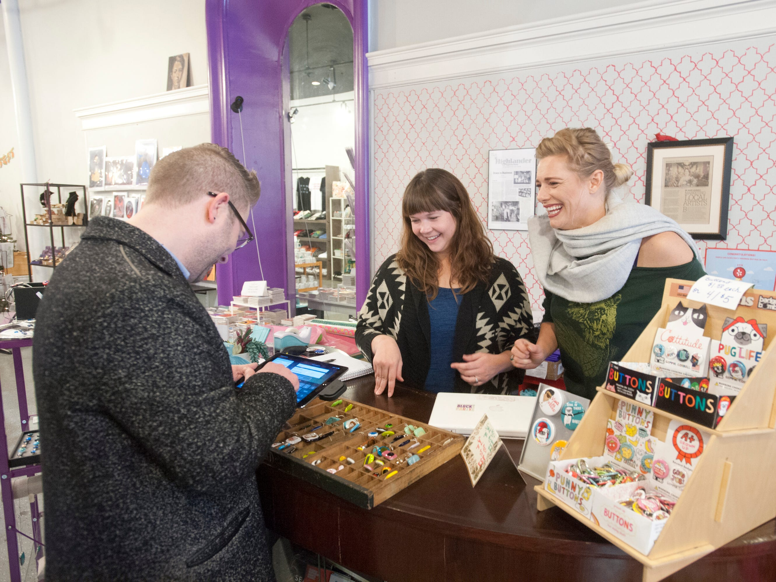 Customer Brian Sayers of Bloomington, Illinois, purchases some punny buttons fro Block Party's Sarah Brown, center, and Malynda November, sales assistant for the store.  24 November 2018