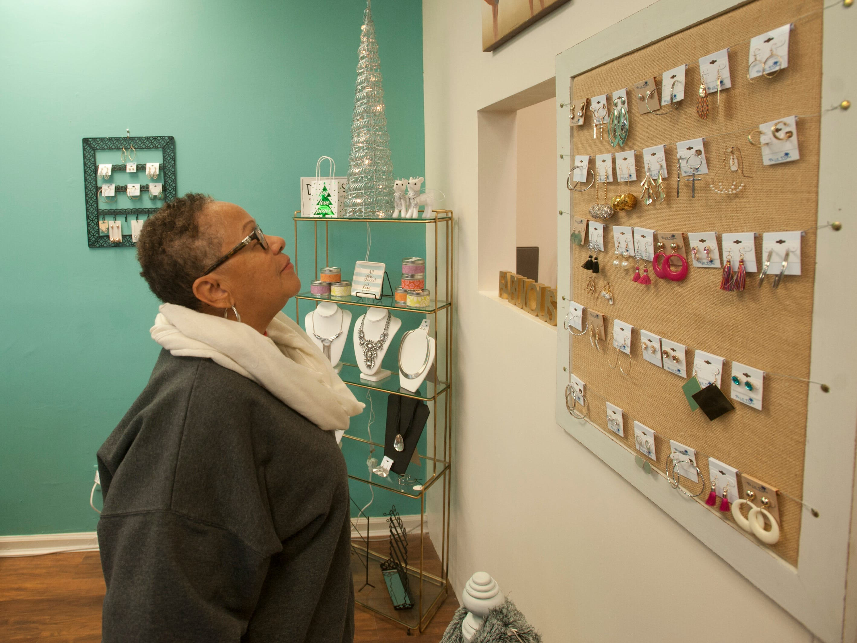 Karen Porter of the Shawnee neighborhood checks out some earrings at Blue Palm Accessories, a women's boutique at 2001 W. Broadway, as part of Louisville's Small Business Saturday. 24 November 2018