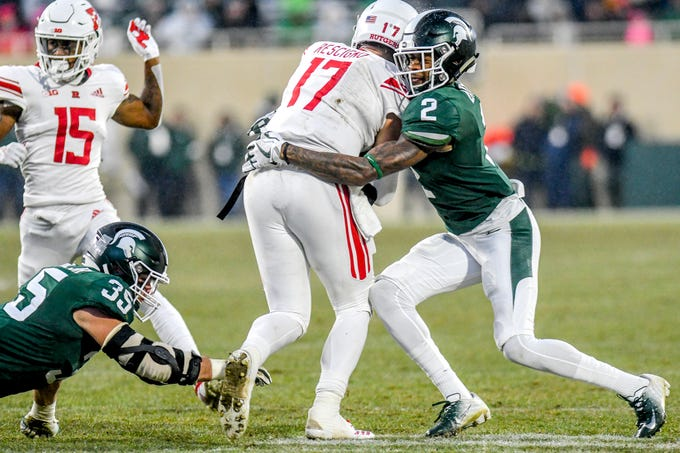 Michigan State's Justin Layne, right, tackles Rutgers quarterback Giovanni Rescigno during the first quarter on Saturday, Nov. 24, 2018, at Spartan Stadium in East Lansing.