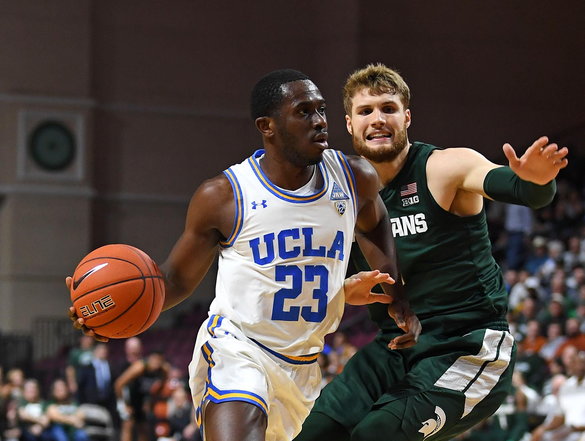 Nov 22, 2018; Las Vegas, NV, USA; UCLA Bruins guard Prince Ali (23) dribbles against Michigan State Spartans forward Kyle Ahrens (0) during the second half at Orleans Arena. Mandatory Credit: Stephen R. Sylvanie-USA TODAY Sports