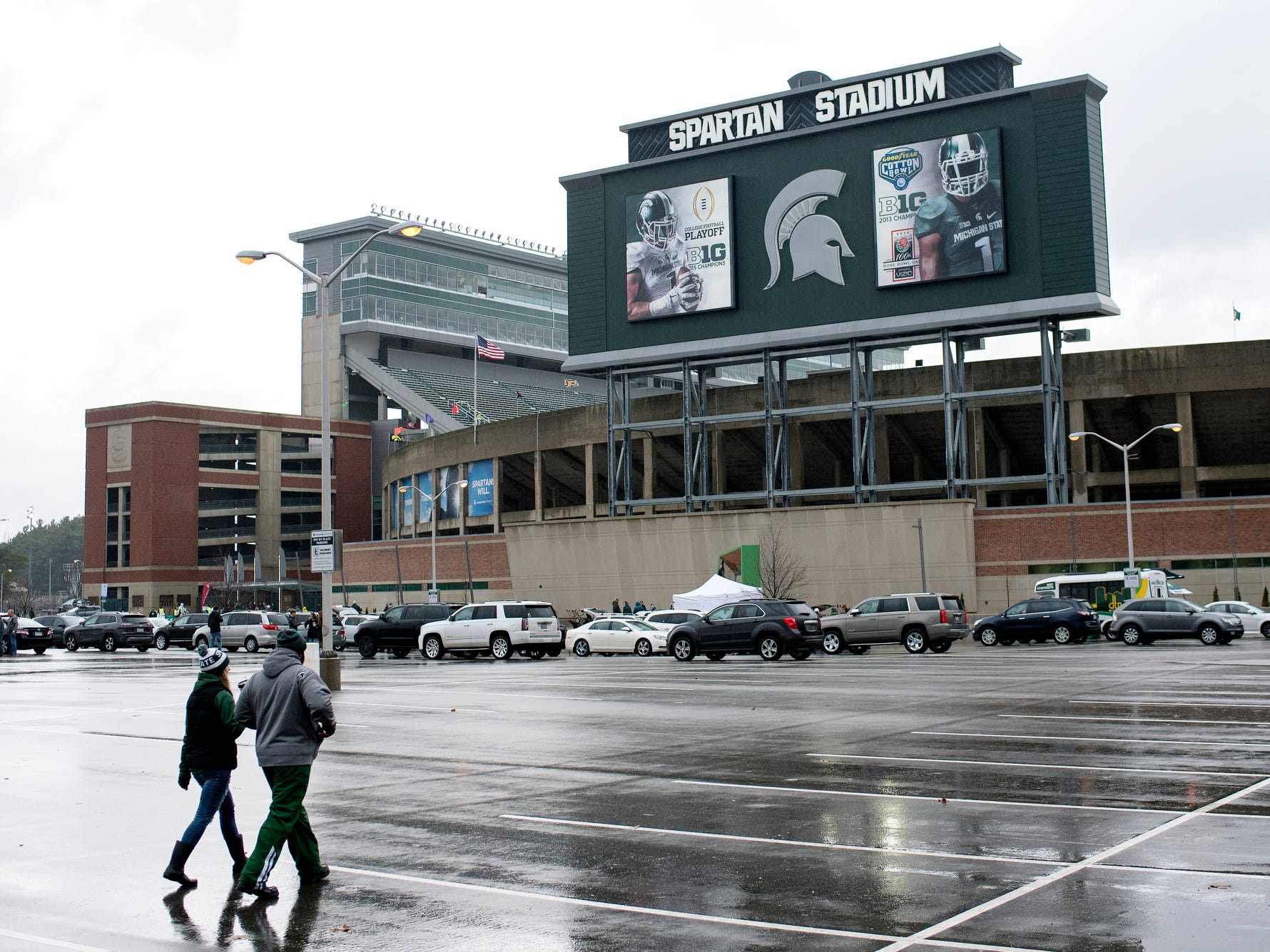 Michigan State fans walk across empty parking spaces on their way to the Spartans game against Rutgers on Saturday, Nov. 24, 2018, at Spartan Stadium in East Lansing.
