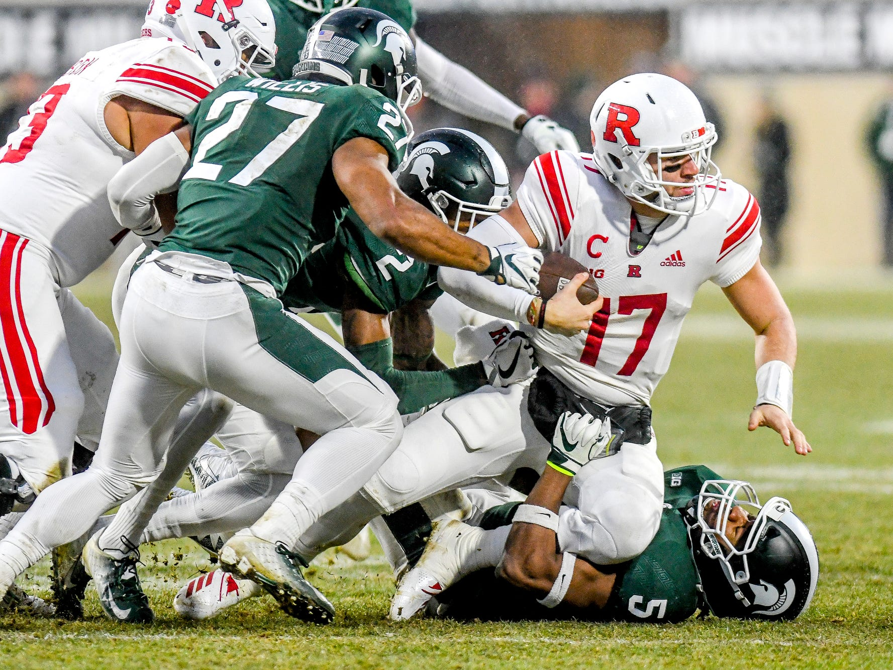 Michigan State's Andrew Dowell, bottom, and other defensive players tackle Rutgers quarterback Giovanni Rescigno during the first quarter on Saturday, Nov. 24, 2018, at Spartan Stadium in East Lansing.