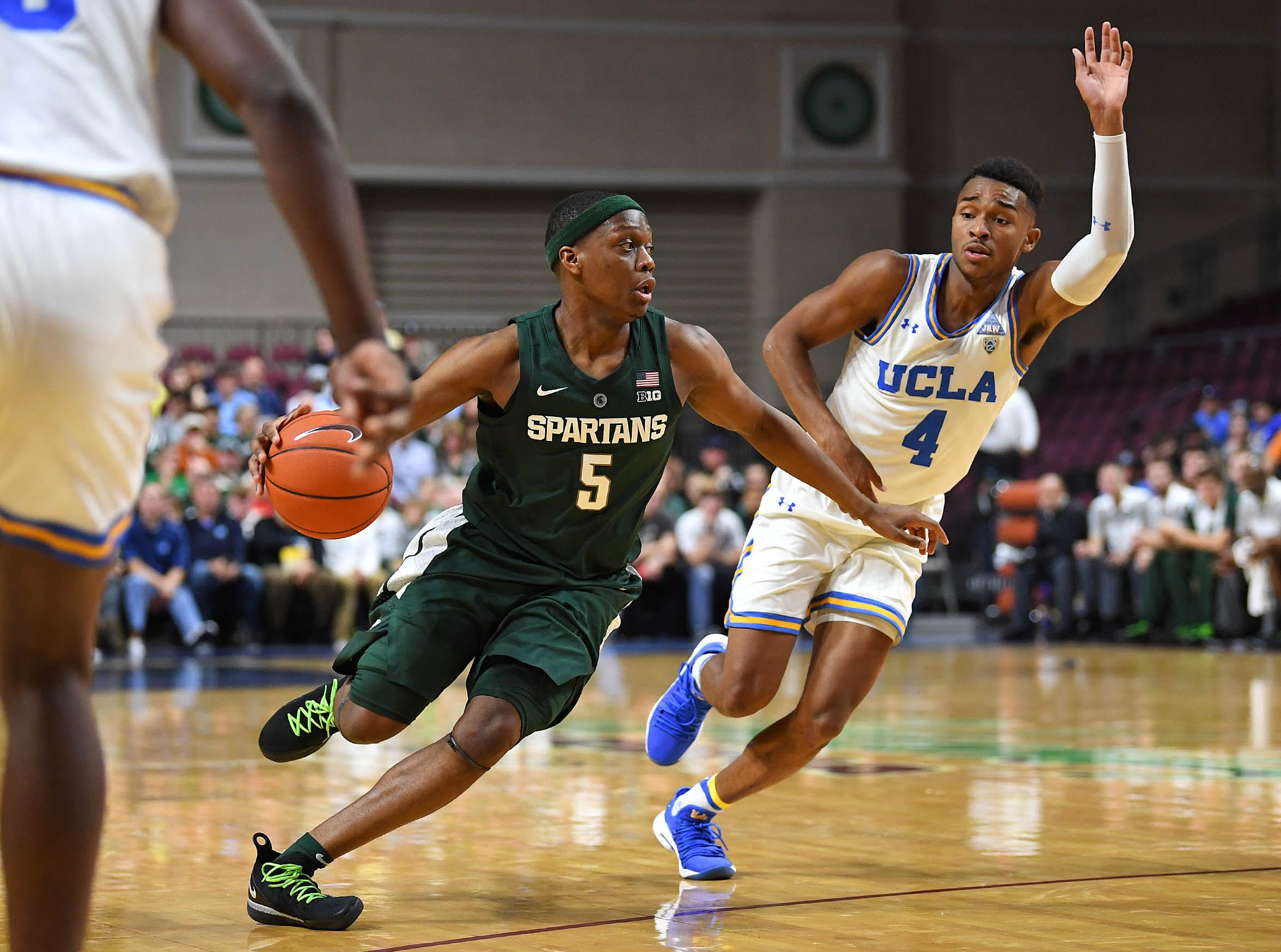 Nov 22, 2018; Las Vegas, NV, USA; Michigan State Spartans guard Cassius Winston (5) dribbles inside the defense of UCLA Bruins guard Jaylen Hands (4) during the first half at Orleans Arena. Mandatory Credit: Stephen R. Sylvanie-USA TODAY Sports