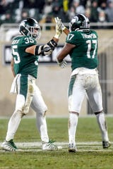 Michigan State's Tyriq Thompson, right, celebrates after a tackle with teammate Joe Bachie during the second quarter on Saturday, Nov. 24, 2018, at Spartan Stadium in East Lansing.