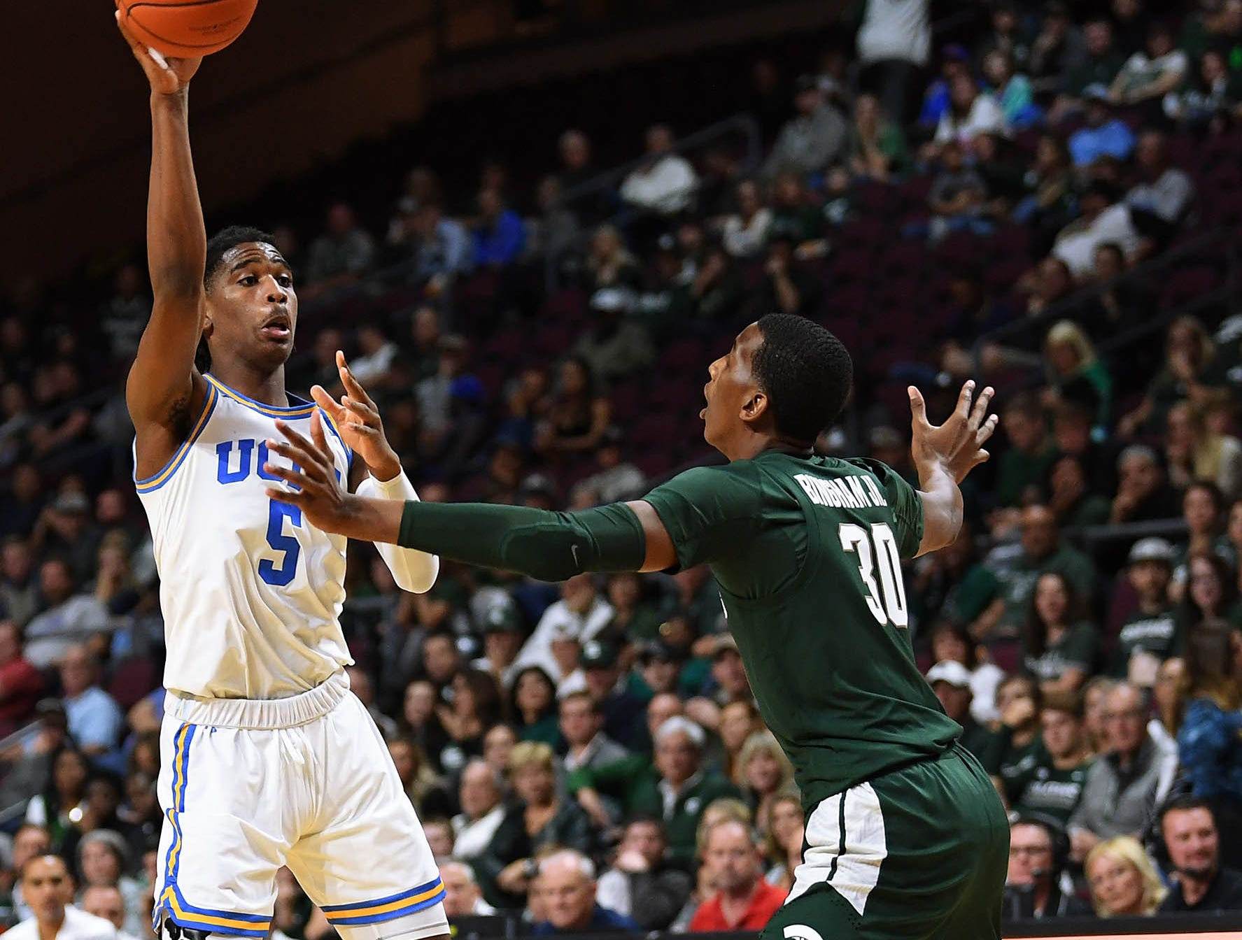Nov 22, 2018; Las Vegas, NV, USA; UCLA Bruins guard Chris Smith (5) passes over the defense of Michigan State Spartans forward Marcus Bingham Jr. (30) during the second half at Orleans Arena. Mandatory Credit: Stephen R. Sylvanie-USA TODAY Sports