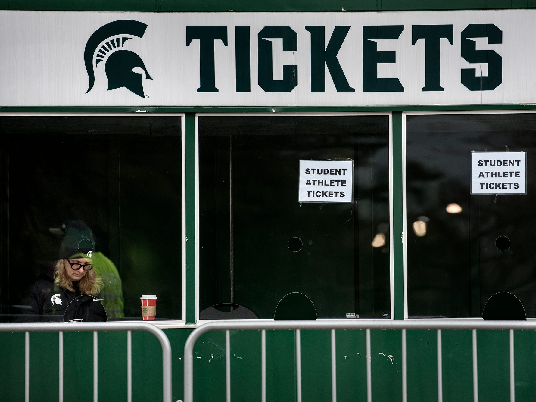 An employee mans a ticket booth that's not seeing much action before Michigan State's game against Rutgers on Saturday, Nov. 24, 2018, outside Spartan Stadium in East Lansing.