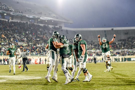 Michigan State's Matt Sokol, left, celebrates with teammates after his touchdown catch during the second quarter on Saturday, Nov. 24, 2018, at Spartan Stadium in East Lansing.